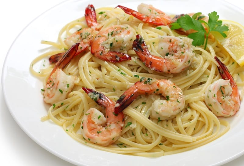 a plate of shrimp scampi on top of spaghetti
