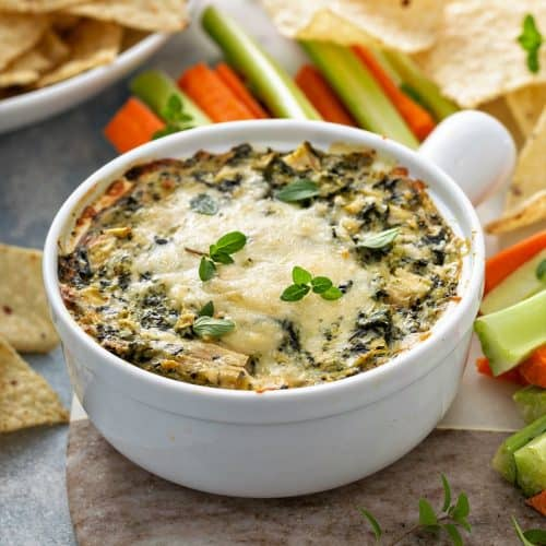 Artichoke spinach dip in a baking dish served with chips and fresh veggies.