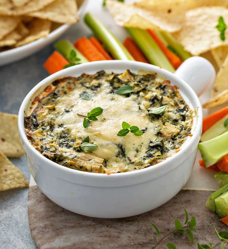 Healthy Artichoke spinach dip in a baking dish served with chips and fresh veggies.