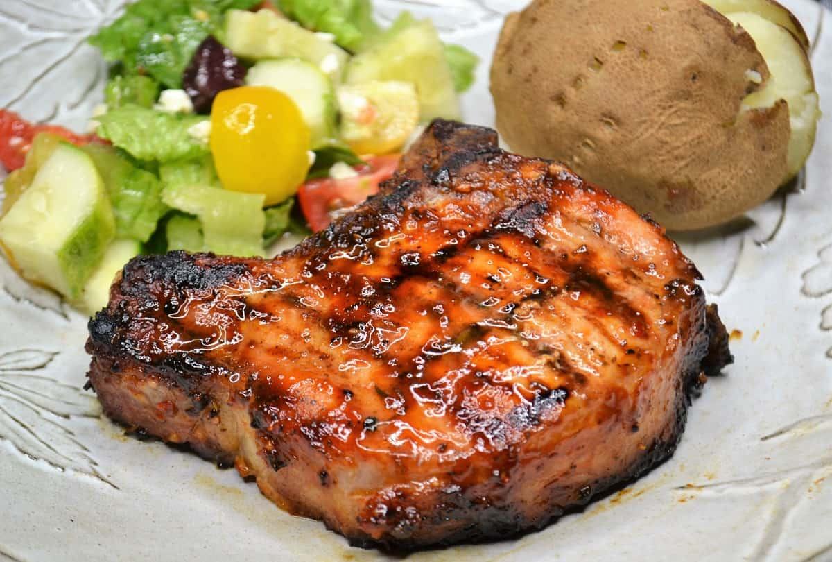pork chop dinner with salad and a baked potato