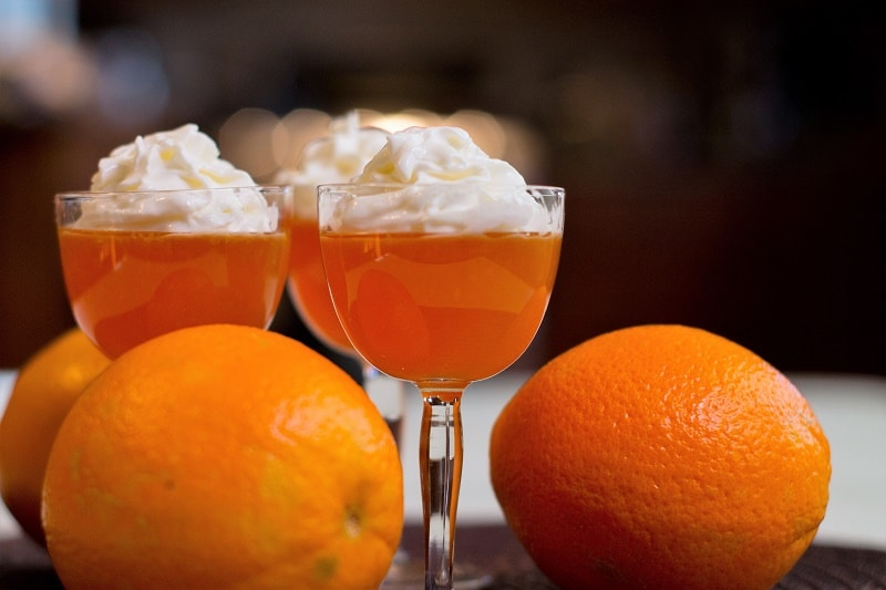 Orange Creamsicle Jello Shots can be made in fancy shot glasses and topped with whipped cream.