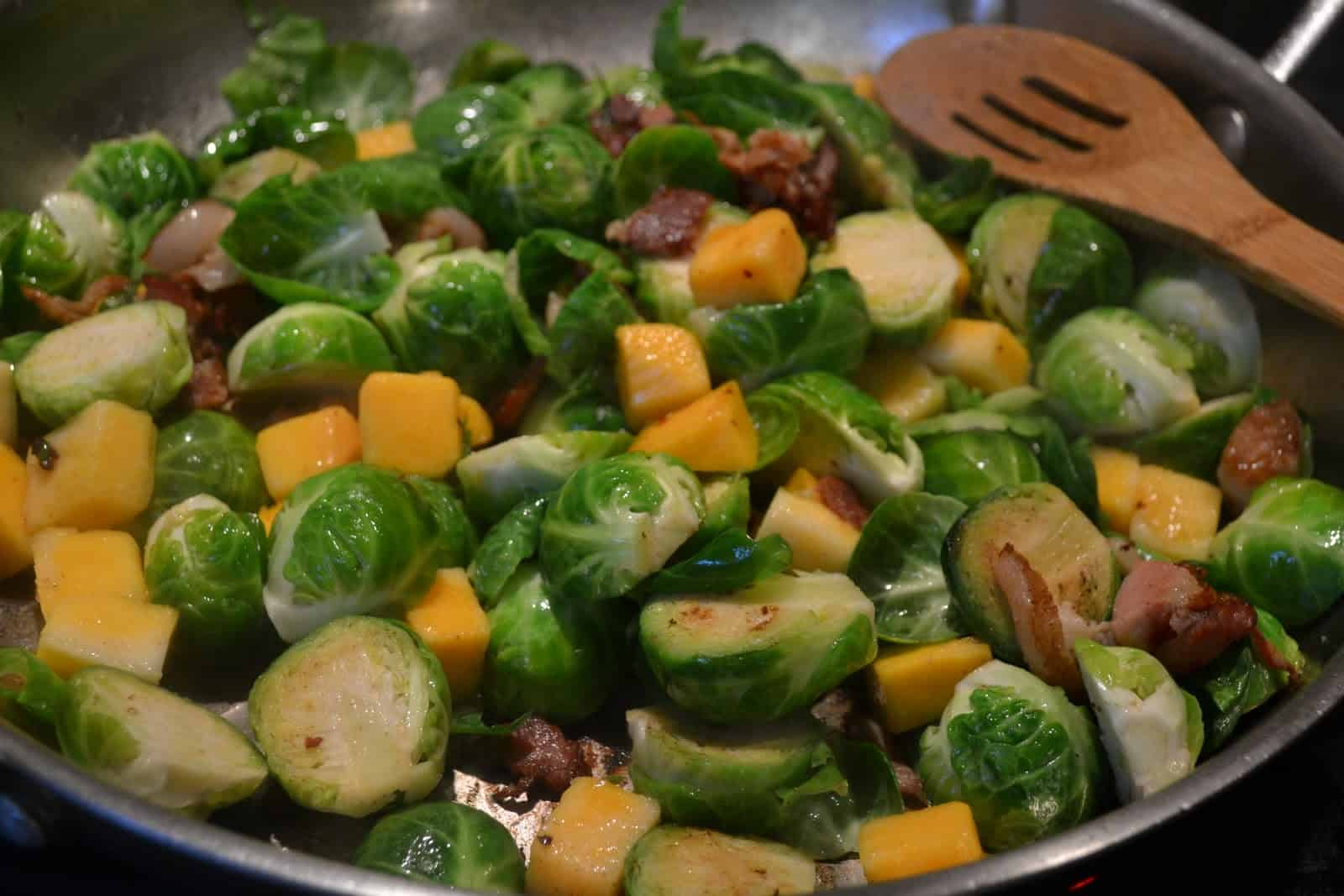 Brussel Sprouts, bacon and butternut squash being sauteed in a pan.