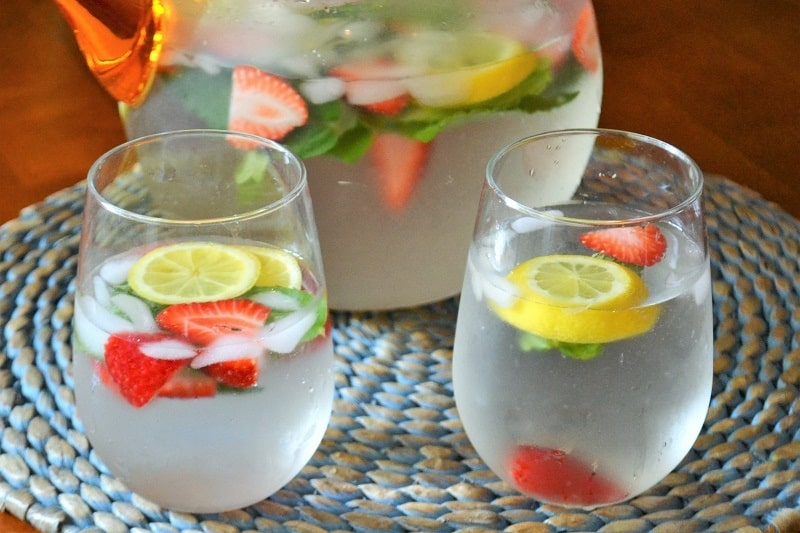 A pitcher of strawberry lemon mint water with two poured glasses