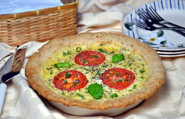 Tomato and Cheese Pie with basil on the table