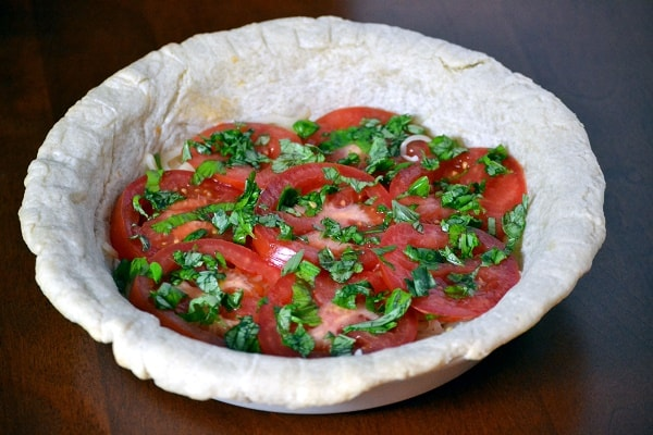 Pie crust unbaked with tomatoes and basil