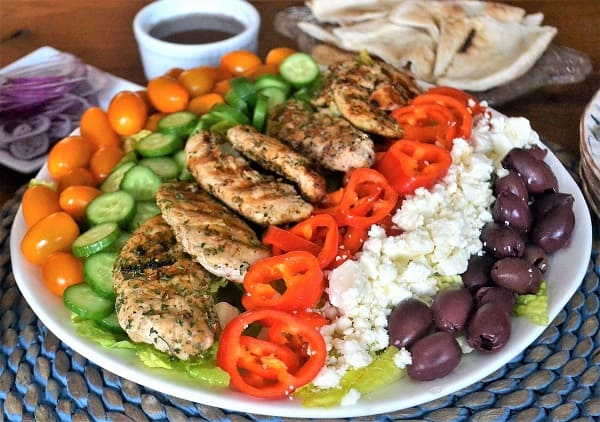 Color full salad with grilled chicken recipe served on a plate.