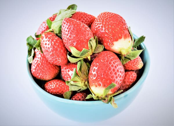 a bright fresh bowl of strawberries are in season