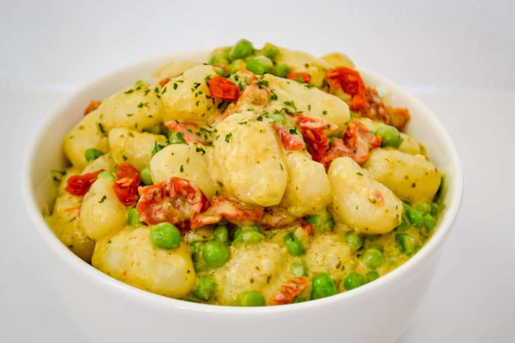 Creamy gnocchi sauce over boiled gnocchi in a bowl.