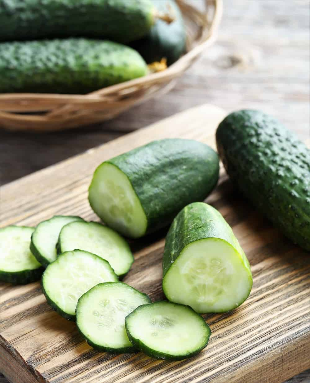 Sliced cucumbers on a board being prepped to make pickles