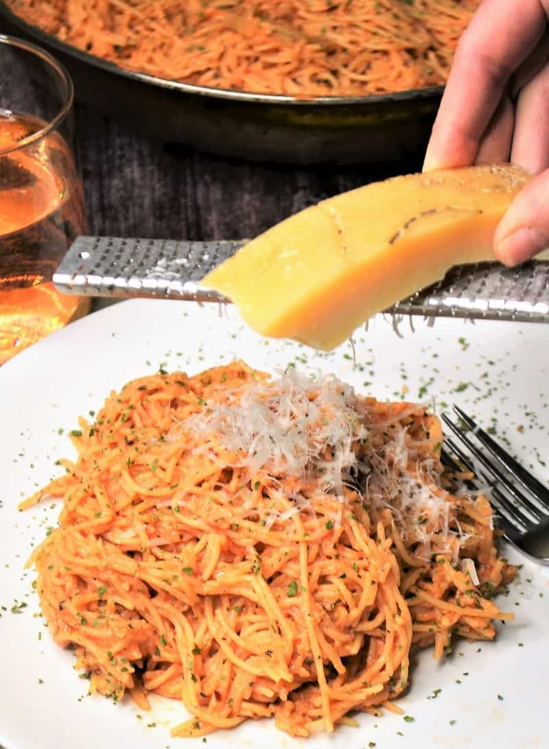 Parmesan cheese being grated over angel hair pasta recipe with creamy tomato sauce