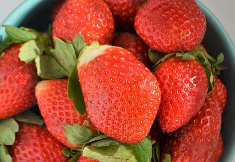teal bowl full of fresh strawberries