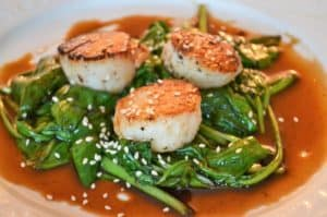 a plate of Asian Seared scallops with spinach
