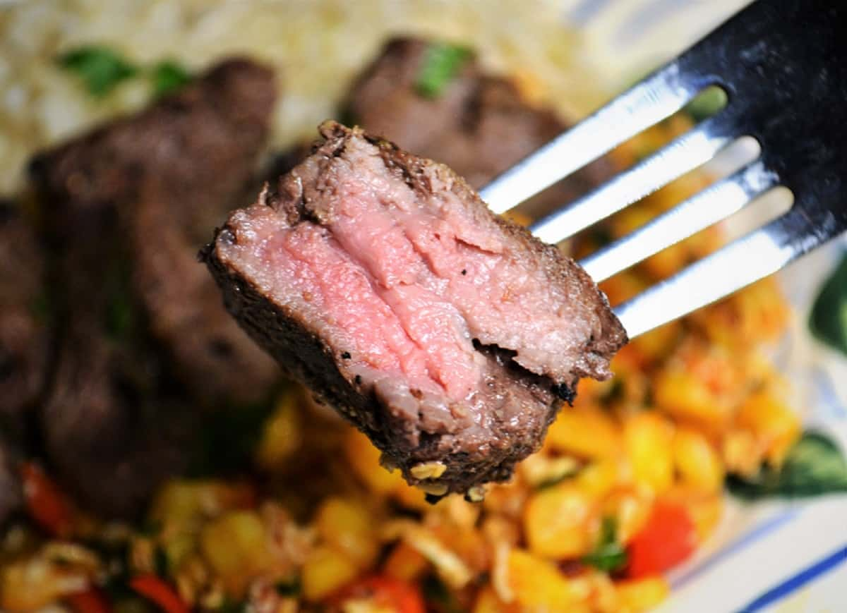 a forkful of steak kabobs with corn salad