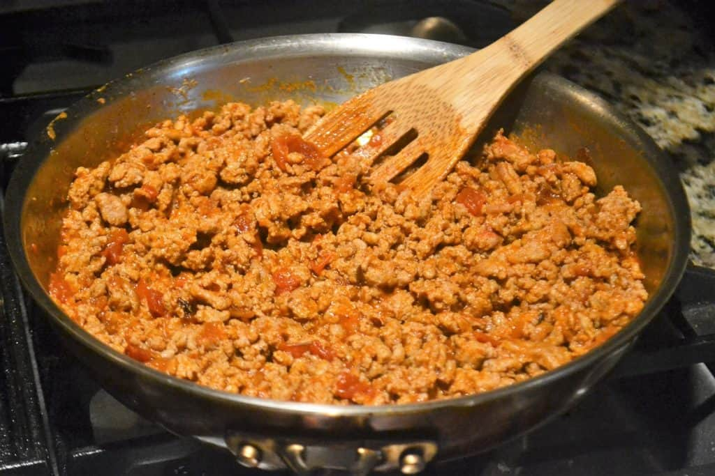 Ground taco meat being sauteed in a pan with taco sauce