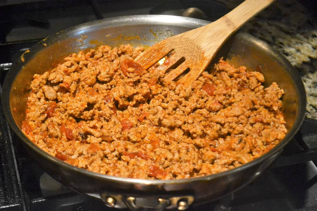 Ground taco meat being sauteed in a pan with taco sauce for these Mexican appetizers.