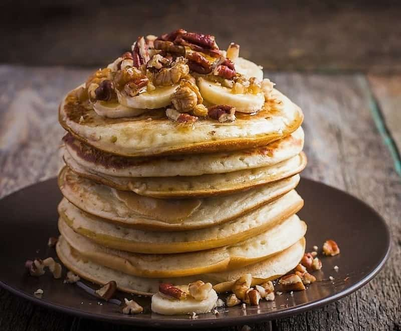 Whole Grain Banana Pecan Pancakes are stacked on a plate with maple syrup.