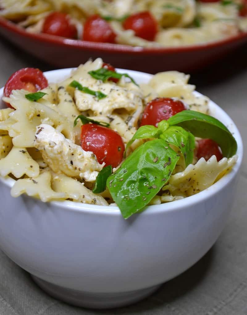 A big bowl of bow tie pasta salad with pesto